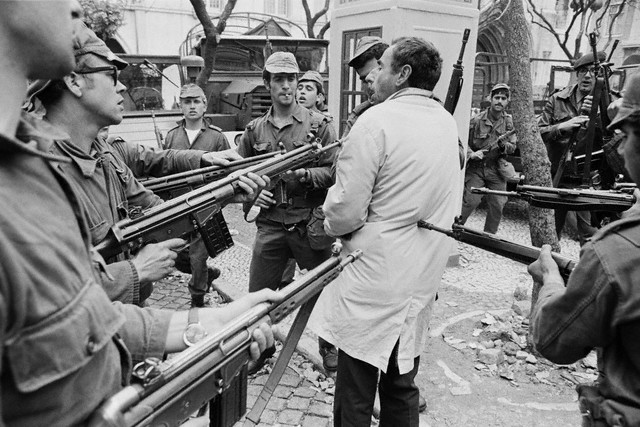 April 1974, Lisbon, Portugal --- A suspected member of PIDE, the secret police, being arrested by soldiers during the Carnation Revolution. --- Image by © Henri Bureau/Sygma/Corbis