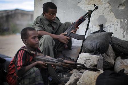 © Ed Ou / Reportage by Getty Images pour The New York Times Prix du Jeune Reporter de la ville de Perpignan 2011 #3. Mogadiscio, 24 avril 2010. Mohamed Adan Ugas (12 ans, à gauche) et Ahmed Hassan (15 ans), enrôlés dans les forces du Gouvernement fédéral de transition, montent la garde à un poste de contrôle près de l'aéroport. Ahmed déclare avoir été envoyé en Ouganda à l'âge de 12 ans pour y être formé. Il s'est fait tirer dessus par le groupe d'insurgés le plus puissant, Al-Shabab.