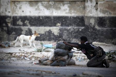 © Ed Ou / Reportage by Getty Images pour The New York Times Prix du Jeune Reporter de la ville de Perpignan 2011 #31. Mogadiscio, Somalie, 4 janvier 2010. Sur la ligne de front, un soldat de 14 ans défend le Gouvernement fédéral de transition contre les insurgés d'Al-Shabab vers le carrefour K4.