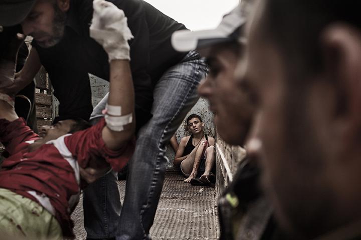 Blessé, un jeune Syrien est assis dans un camion après une attaque menée par les forces du président Assad sur le quartier de Shaar. Le camion est utilisé pour transporter les victimes et les blessés à l'hôpital. Selon les Nations Unies, plus de 70.000 personnes sont mortes en 2 ans de guerre civile en Syrie. 21 octobre 2012 - Syrie (c) Fabio BUCCIARELLI / AFP