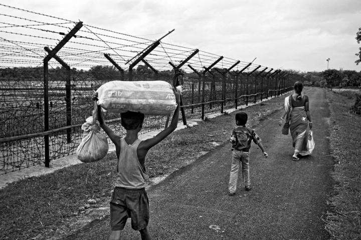 Inde, Province du Bengale-Occidental, 30 mai 2013 Dans la région de Balurghat, une mère et ses deux enfants vont rendre visite à des membres de leur famille habitant dans un village voisin, à proximité de la clôture. © Gael Turine / Agence VU