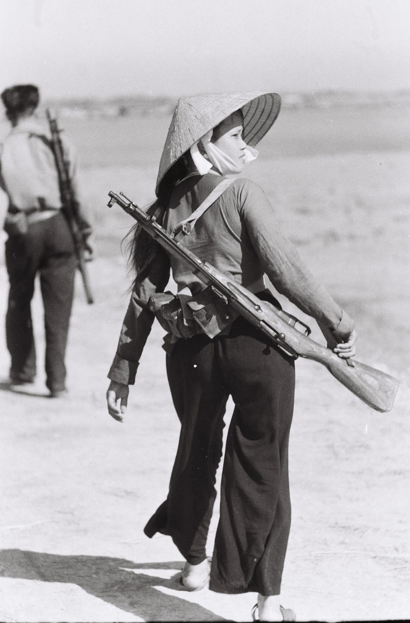1966. À 19 ans, Nguyen Thi Hien est chef de l'escouade de la milice à Yen Vuc, district de Ham Rong, province de Thanh Hoa. Elle a survécu à plus de 800 raids aériens et a été enterrée vivante à quatre reprises lors des explosions des bombes de B-52. © Maï Nam