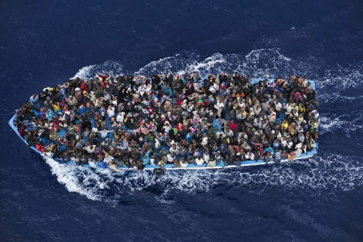 """Une embarcation de migrants venus de Libye est escortée par la marine italienne dans le cadre de l'opération """"Mare Nostrum"""", le 7 juin 2014 - Catégorie """"Actualités""""  (c) Massimo Sestini"""