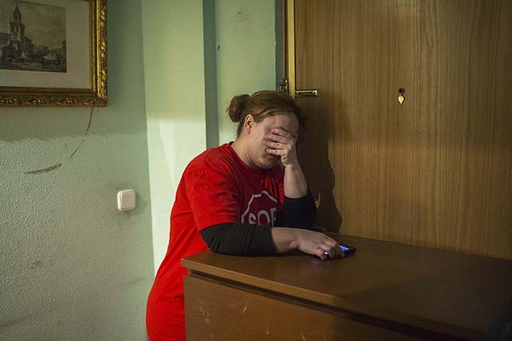Rosario Echevarria Pedrezuela, 35, leans on a piece of furniture blocking the entrance door as the police prepare to break into the apartment in Madrid, Spain, Monday, Feb. 16, 2015. The apartment occupied by Echevarria Pedrezuela, her husband Angel Echevarria Gabarri, 35, and their two children, aged 5 and 8 belongs to Bankia bank, after the previous owner was unable to continue paying the mortgage. The family occupied the foreclosed apartment ten months ago after they were evicted from their previous home. With both Echevarria Pedrezuela and her husband being unemployed and the family's sole income being a state benefit of euro 530 ($ 604), they could not afford to pay rent. Attempts to negotiate a low rent with the bank were turned down, resulting in the family's eviction by police. (AP Photo/Andres Kudacki)