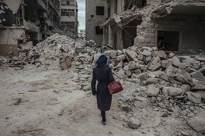 """Une jeune femme marche dans les dŽcombres juste aprs qu'une bombe """"baril"""", larguŽe par le rŽgime, ait explosŽ dans le quartier de Saif Al-deawla, au sud ouest d'Alep, SYRIE 03/05/2015 Durant toute la durŽe de mon reportage a Alep, je logeais chez un soldat de l'ArmŽe Syrienne Libre. Nous Žtions quatre a vivre sous son toit. Le premier jour, alors que nous prenions notre petit dŽjeuner, (il Žtait 9h du matin) nous avons entendu des bombes exploser au loin puis nous avons entendu un Žnorme sifflement. Une bombe venait d'tre larguŽe au dessus de nous. Tout le monde a couru dans le cuisine pour tenter d'y trouver refuge. Je n'ai pas couru avec eux, je suis restŽ sans bouger en me disant que si la bombe devait tomber sur notre b‰timent, je ne pouvais pas Žchapper a une mort certaine. Apres un gros """"boum"""", j'ai rŽalisŽ que la bombe n'Žtait pas tombŽe sur nous. En rŽalitŽ elle avait explosŽ 200 mtres plus loin, sur une Žcole. Plusieurs enfants sont morts dans cette explosion ce jour laÉ Apres cette explosion, j'ai du partir rapidement car j'avais rendez-vous dans la prison pour rencontrer les deux prisonniers afghans. Ce n'est qu'en revenant (5 heures plus tard) que j'ai vu cette jeune femme, comme une apparition. Elle semblait chercher quelqu'un dans les dŽcombres."""