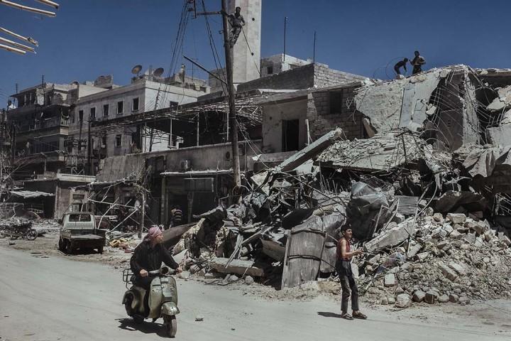 Les passants regardent les dŽcombres de l'Žcole dŽtruite par une bombe baril (larguŽe par les forces gouvernementales) dans le quartier de Saif Al-deawla, au sud ouest d'Alep, SYRIE 03/05/2015