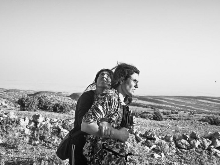 IRAQ. Sinjar Mountains. August 12, 2014. Yazidi women stranded in the Singar Mountains wait for the arrival of a rescue helicopter. Discordia-Moises-Saman