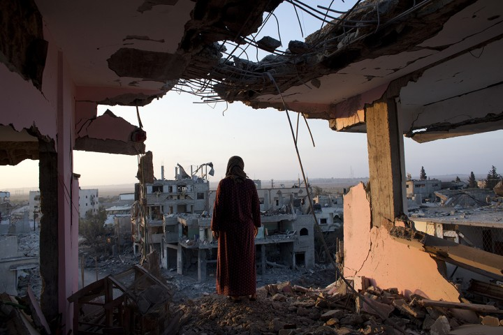Palestinian woman Hidya Atash stands on the top floor of her home as she overlooks the destruction in the Shujayea district of Gaza City just after dawn Aug. 8, 2014.Her family's home was hit by a warning rocket fired by the Israeli air force and the family of 40 people fled . When the family was able to return back to their home during a temporary cease fire , they discovered their home was heavily damaged during the fighting .(Photo by Heidi Levine /Sipa Press).