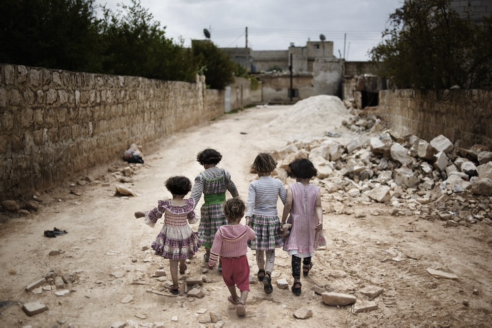SYRIA, Idlib province: Children walk down a street in Killi, a town in Idlib province, a few days after troops of the Al Assad regime entered  the village to destroy and burn houses of allegedly pro revolution activists on April 11, 2012. (c) Alessio Romenzi
