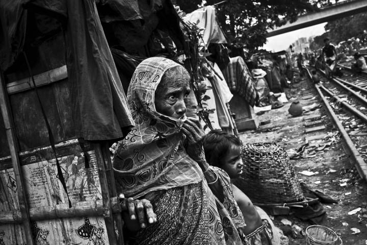 Bangladesh, Dacca, 02 septembre 2012 - Jotana, 65 ans, est arrivée à Dacca une semaine auparavant. Elle a rejoint son fils qui vit dans un quartier pauvre depuis trente ans. Elle vient de la région frontalière de Sathkira mais elle ne pouvait pas subvenir seule à ses besoins dans son village d'origine. Ses deux autres fils sont contrebandiers et elle ne les voit plus car ils doivent se cacher des gardes-frontières du Bangladesh. Le quartier est dangereux à cause des trains qui passent près des maisons. Les accidents impliquant les enfants et les personnes âgées sont assez fréquents. © Gael Turine / Agence VU