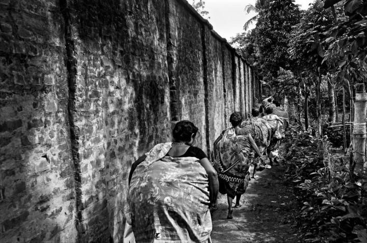 India, West Bengal Province, Hili 29 May 2013 The border town of Hili is highly guarded by the Indian Border security Force (BSF) because it's an official point of passage for the trucks. Bangladeshi women carrying bags full of goods, are walking along the border wall that runs along the city. They just bought Indian goods (spices, jewels, make-up...) that they will sell in Bangladesh. They prefer to travel as a group in order to escape easier if a BSF soldier is coming. Inde, Province du Bengale-Occidental, Hili, 29 mai 2013 A Hili, ville frontalière dotée d'un point de passage officiel pour les camions de marchandises et donc hautement surveillée par la Indian Border security Force (BSF). Un groupe de Bangladaises, passé illégalement en Inde, courent au pied du mur-frontière érigé tout le long de la ville. Elles ont acheté des marchandises indiennes (épices, bijoux, produits de beauté, médicaments,...) qu'elles revendront au Bangladesh. Elles préfèrent effectuer ce type de passage en groupe de manière à pouvoir s'éparpiller et s'échapper plus facilement si un soldat de la BSF intervient. Gael Turine / Agence VU