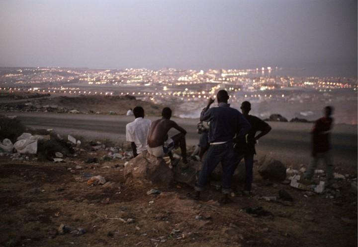 """""""De la décharge d'ordures, située près du camp, on peut voir l'Espagne. Les camarades viennent là et ils rêvent. L'une des façons de se retrouver en Europe est de franchir les barrières, de 4 mètres de haut,dont on peut voir les lumières. Mais les passeurs prennent cher. """" Texte de Kingsley Abang Kum"""