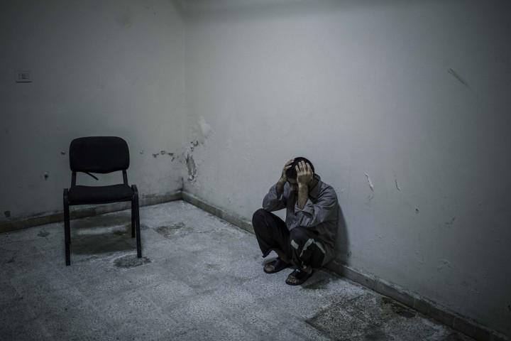 Said Ahmed Hussein (23 ans), prisonnier afghan, reste muré dans le silence dans la prison de Jibha al-Shamiya située à l'est d'Alep. Il a été fait prisonnier par l'Armée Syrienne Libre en octobre 2014 à Almallah, au nord d'Alep. Alep - SYRIE 03/05/2015 Quand je suis arrivé dans leur cellule, j'ai vraiment été marqué par leurs regards infiniment tristes. Ils avaient les yeux plongés dans le vide et ne bougeaient pas. Une odeur tenace d'humidité régnait dans la pièce. On les avait habillé avec de nouvelles chemises, comme s'il fallait qu'il soient présentables pour l'interview ou pour montrer qu'ils étaient bien traités. Ils nageaient dans ces chemises, bien trop grandes pour eux. Cette photo a été prise après l'interview. Je suis resté 1h ou 2 avec eux, dans le silence le plus complet. Ils ne m'adressaient la parole que pour me demander des cigarettes. Ils ne s'arrêtaient pas de fumer. Alors je me suis assis et j'ai fumé avec eux, toujours dans le silence. Apres un moment, il fallait que je parte pour prendre des photos a Alep. Apres leur avoir laissé mon paquet de cigarettes, nous nous sommes serrés la main, sans un mot. Et je suis parti.